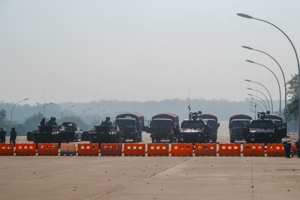 Myanmar's military stand guard at a checkpoint manned with armored vehicles blocking a road leading to the parliament building Tuesday, Feb. 2, 2021, ...