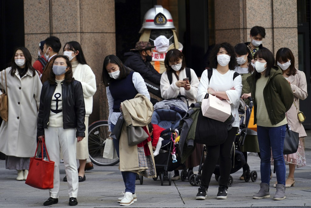 People wearing protective masks to help curb the spread of the coronavirus wait for a traffic light at an intersection Monday, March 1, 2021, in Tokyo...