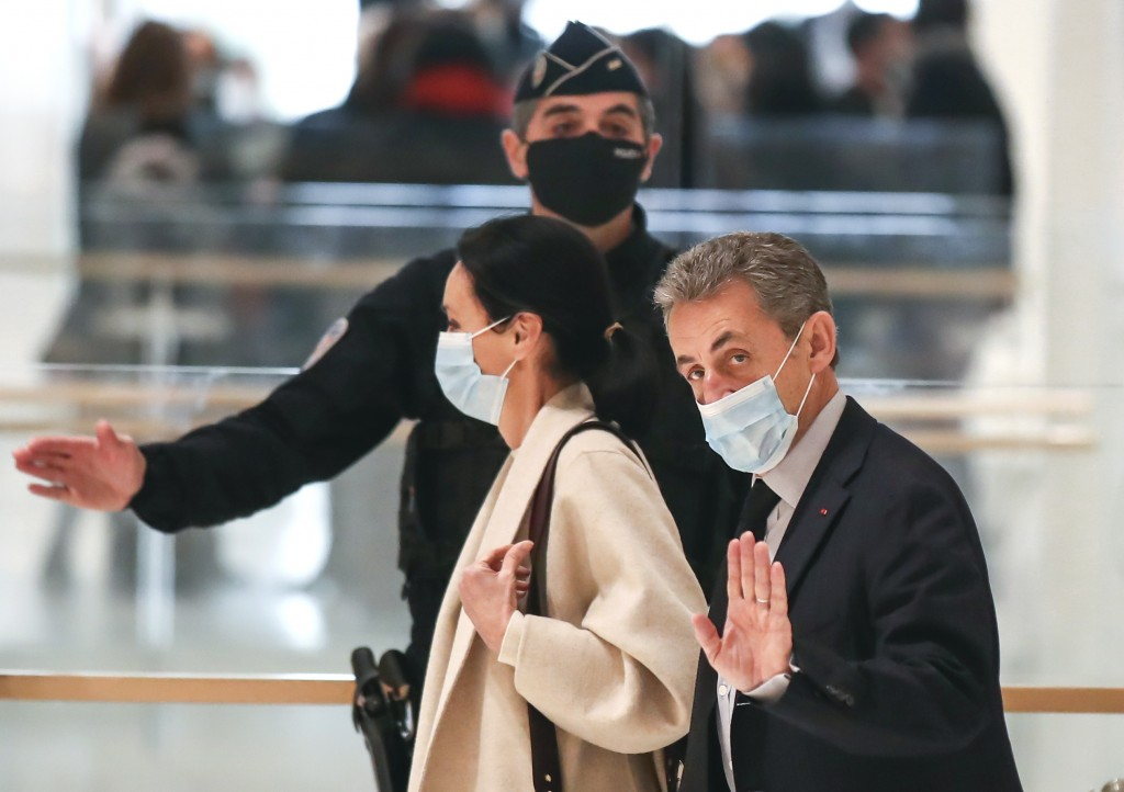 FILE - In this Dec.10, 2020 file photo, former French President Nicolas Sarkozy waves to the media as he arrives at the courtroom in Paris. The verdic...