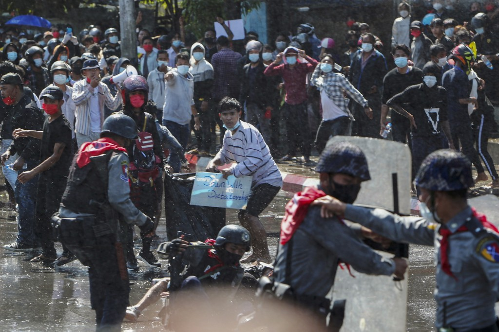 Protesters run after police shot warning shots and used water cannon to disperse them during a protest in Mandalay, Myanmar, Tuesday, Feb. 9, 2021. In...
