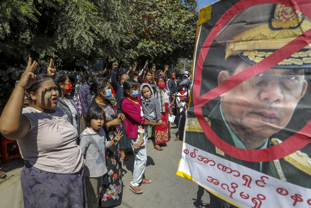 Demonstrators shout slogans and flash the three-fingered symbol of resistance against the military coup standing next to a defaced image of Myanmar mi...