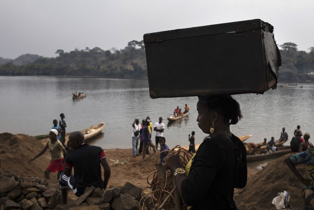 An unidentified woman carries her belongings on her head after crossing the Mbomou river back into Bangassou, Central African Republic, from Ndu in th...