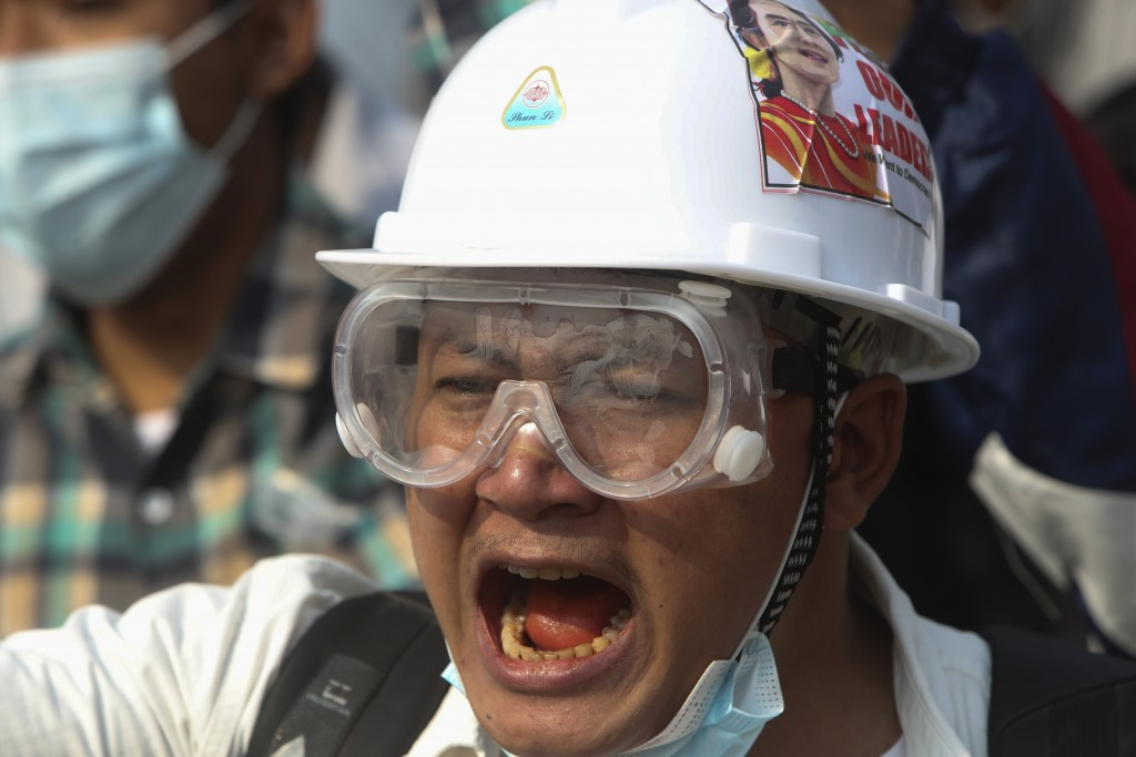 A protester wears a safety helmet and eye protector as he shouts slogans during a protest against a military coup in Yangon, Myanmar, Sunday, Feb. 28,...