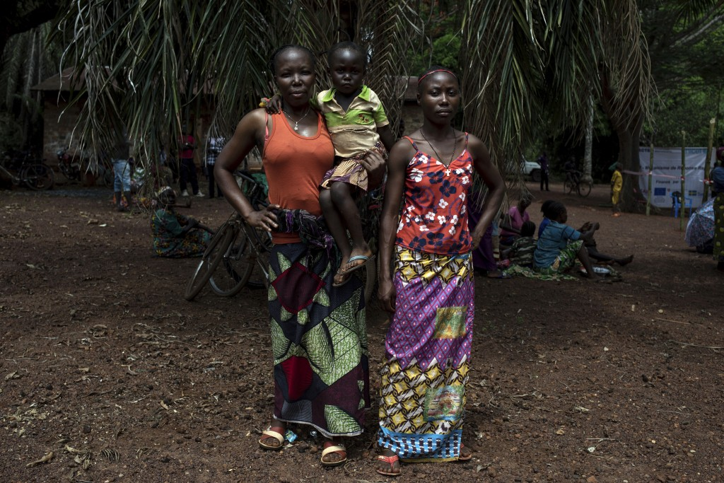 Monique Moukidje, 34, left, poses for a picture with her two children Marienne and Odalvia, in Mbangui-Ngoro, a Central African Republic village where...