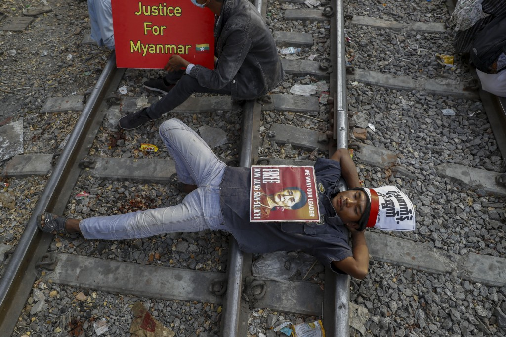 Demonstrators with placards lie on the railway tracks in an attempt to disrupt train service during a protest against a military coup in Mandalay, Mya...