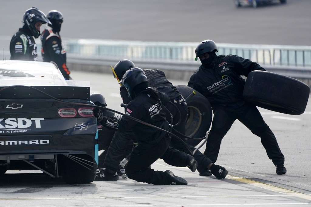 The number 53 car driven by Garrett Smithley gets new tires during a pit stop during a NASCAR Cup Series auto race, Sunday, Feb. 28, 2021, in Homestea...