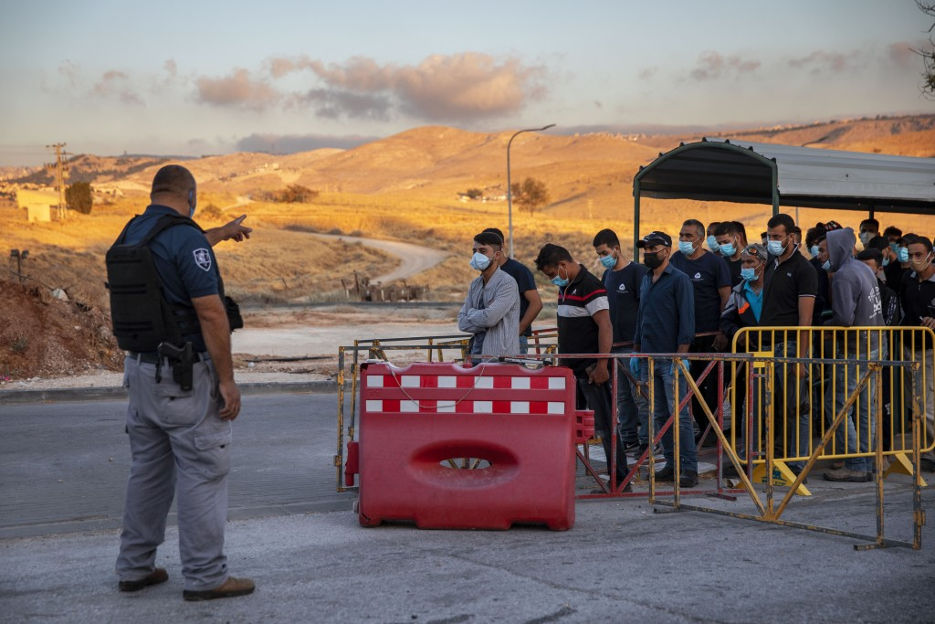 FILE - In this June 30, 2020 file photo, Palestinian laborers line up to cross a checkpoint at the entrance to the Israeli settlement of Maale Adumim,...