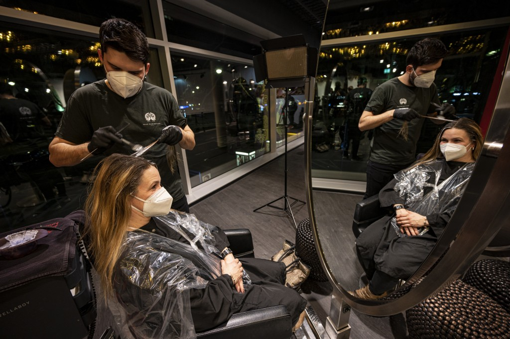 The first customer of Shan Rahimkhan's barbershop gets her hair cut and colored after the reopening in Berlin, Germany, early Monday, March 1, 2021. H...