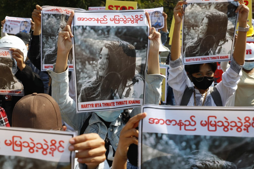 Mandalay University graduates hold posters with an image of Mya Thwet Thwet Khine, a young woman shot by police on Feb. 9 in Naypyitaw, during an anti...