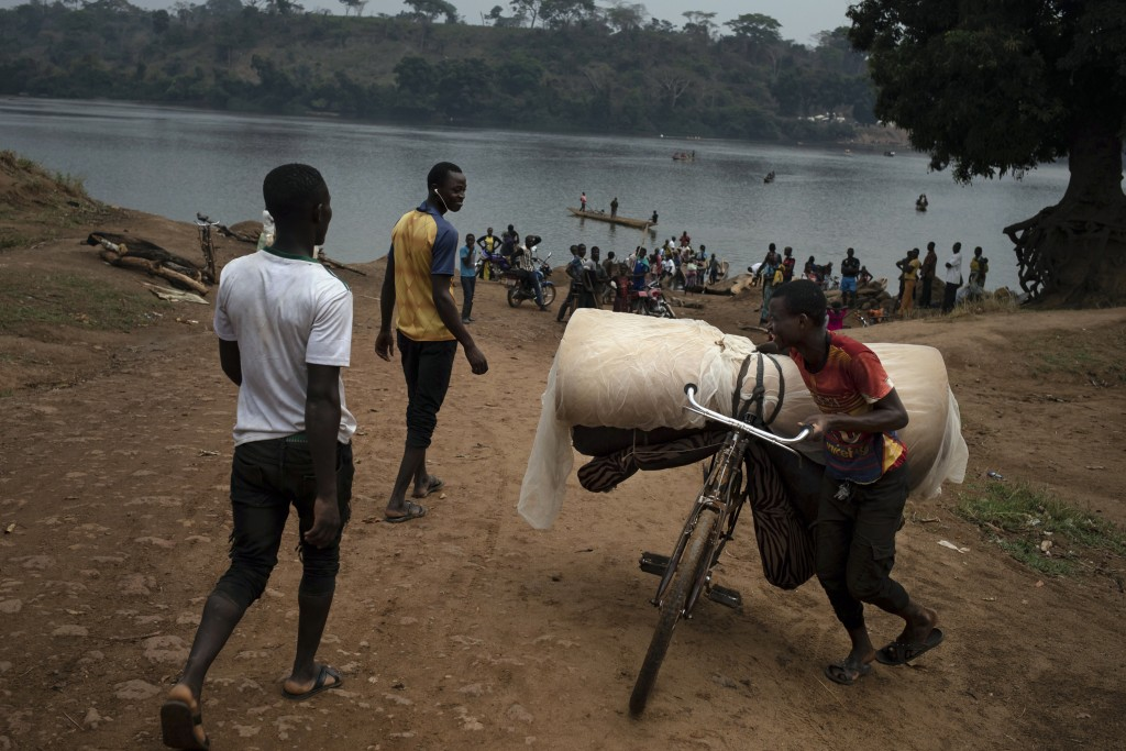Jeremy Kowomando, 32, and his 14-large family, cross the Mbomou river back into Bangassou, Central African Republic, from Ndu in the Democratic Republ...