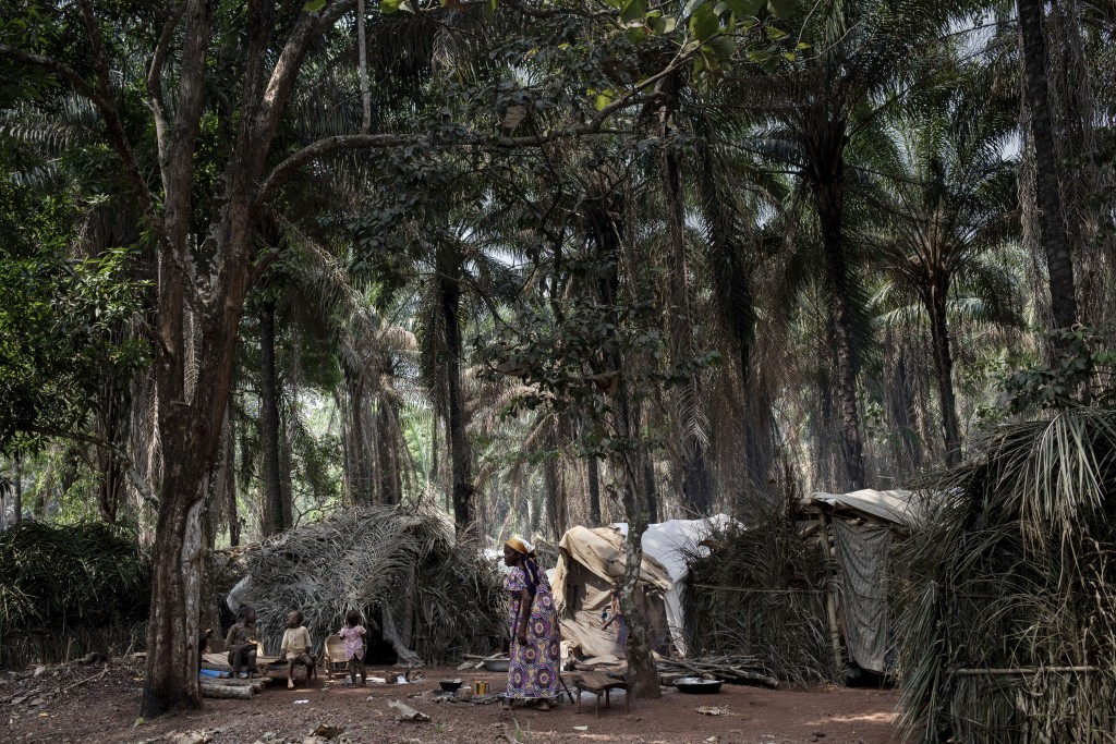 Displaced woman and children stand by their makeshifts shelter in the village of Cesacoba, Central African Republic, Sunday Feb. 14, 2021. An estimate...