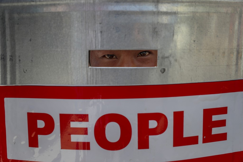 An anti-coup protester watches through a shield after police blocked their march in Mandalay, Myanmar, Wednesday, Feb. 24, 2021. In the month since Fe...