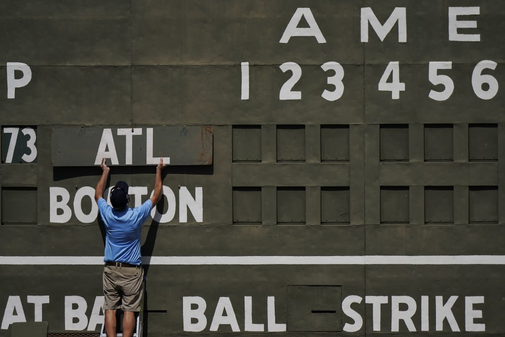 An attendance places the Atlanta Braves sign on the Green Monster score board before a spring training baseball game against the Boston Red Sox on Mon...