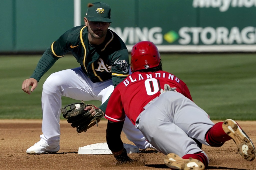 Oakland Athletics' Pete Kozma tags out Cincinnati Reds Alex Blandino (0) on a steal attempt during the first inning of a spring training baseball game...