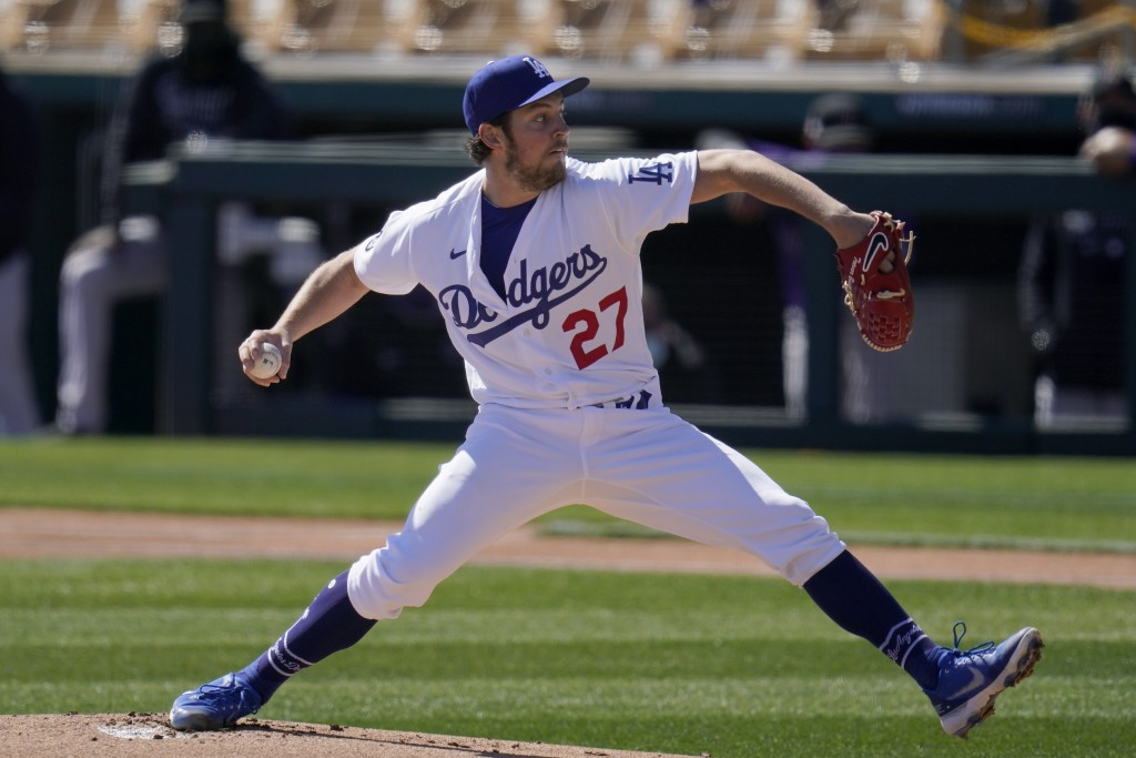 Los Angeles Dodgers starting pitcher Trevor Bauer throws against the Colorado Rockies during the first inning of a spring training baseball game Monda...