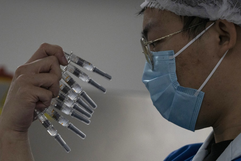 FILE - In this Thursday, Sept. 24, 2020 file photo, a worker inspects syringes of a vaccine for COVID-19 produced by Sinovac at its factory in Beijing...