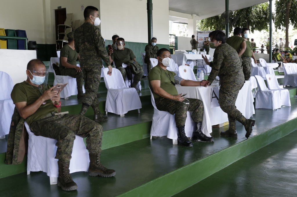 Philippine Army soldiers rest after being injected with the Sinovac vaccine from China during a vaccination at Fort Bonifacio, Metro Manila, Philippin...
