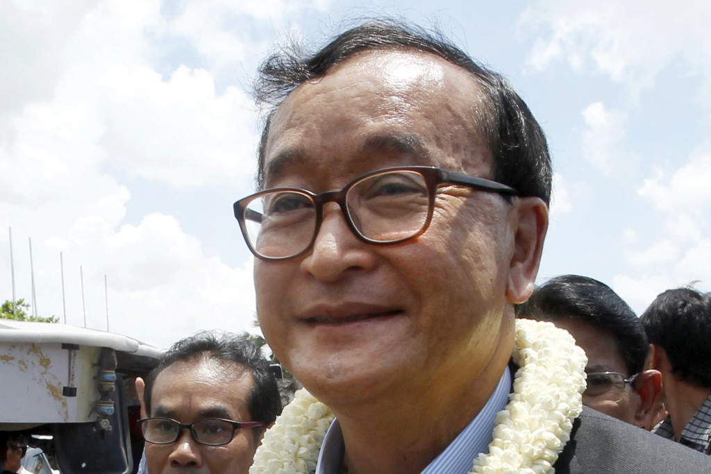 FILE - In this Aug. 16, 2015, file photo, Sam Rainsy, leader of the opposition Cambodia National Rescue Party, greets his party supporters upon his ar...