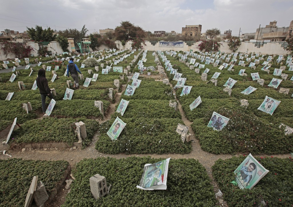 Yemeni men walk amid the graves of Houthi fighters who were killed during recent fighting, at a cemetery in Sanaa, Yemen, Tuesday, Mar. 2, 2021. (AP P...