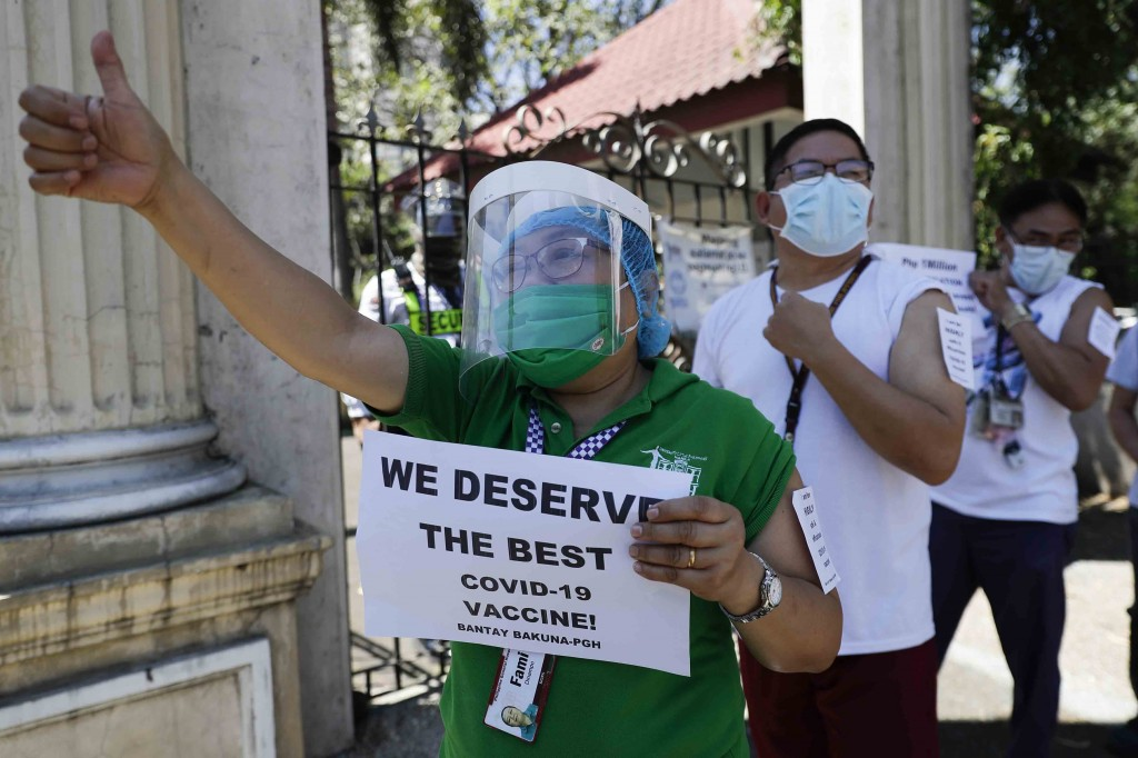 FILE - In this Friday, Feb. 26, 2021 file photo, a health worker wearing a face mask and shield holds a sign as she and others call on the government ...