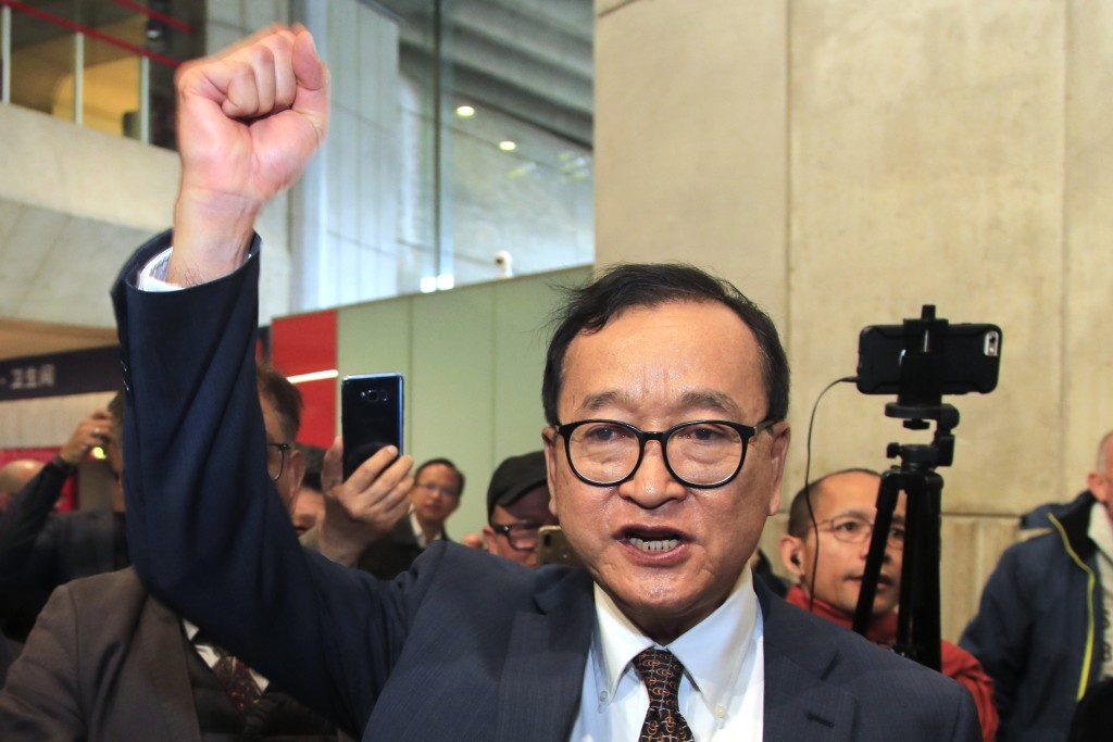 FILE - In this Nov. 7, 2019, file photo, Cambodia's most prominent opposition politician Sam Rainsy clenches his fist as he is attempting to return to...