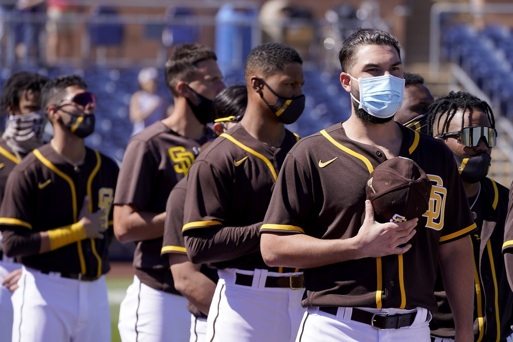 Players for the San Diego Padres stand for the national anthem before a spring training baseball game against the Chicago Cubs, Monday, March 1, 2021,...