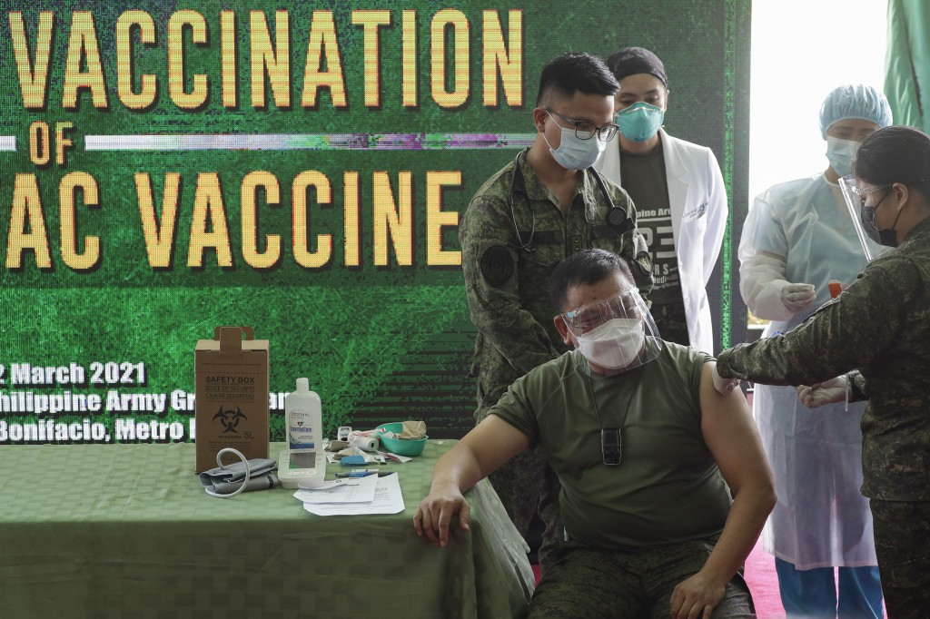 Philippine Army commander, Lt. Gen. Jose Faustino Jr., front left, is injected with the Sinovac vaccine from China during the start of vaccination at ...