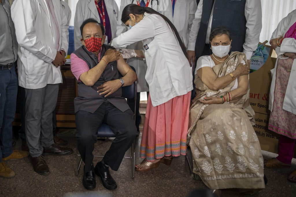Indian Health Minister Harsh Vardhan is administered the COVAXIN vaccine, developed by Indian company Bharat Biotech, with his wife Nutan Goel sitting...