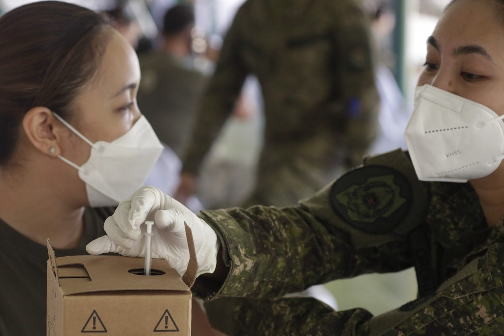 An army doctor disposes the syringe used to inject the Sinovac vaccine from China during a vaccination at Fort Bonifacio, Metro Manila, Philippines on...