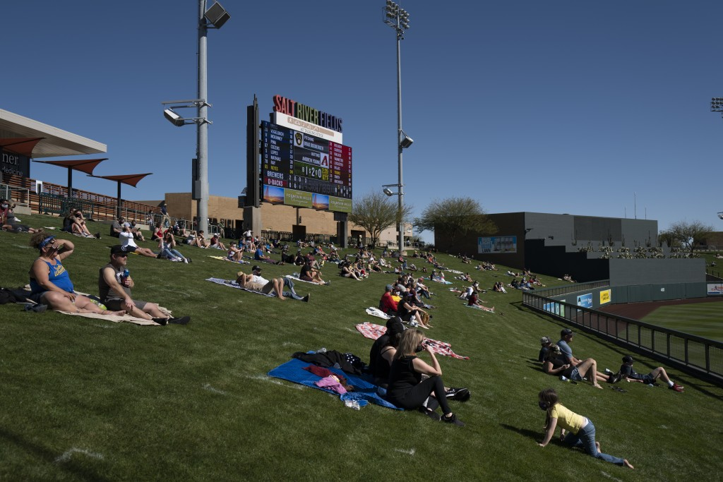 Socially distanced fans watch a spring baseball game between the Arizona Diamondbacks and the Milwaukee Brewers in Scottsdale, Ariz., Monday, March 1,...