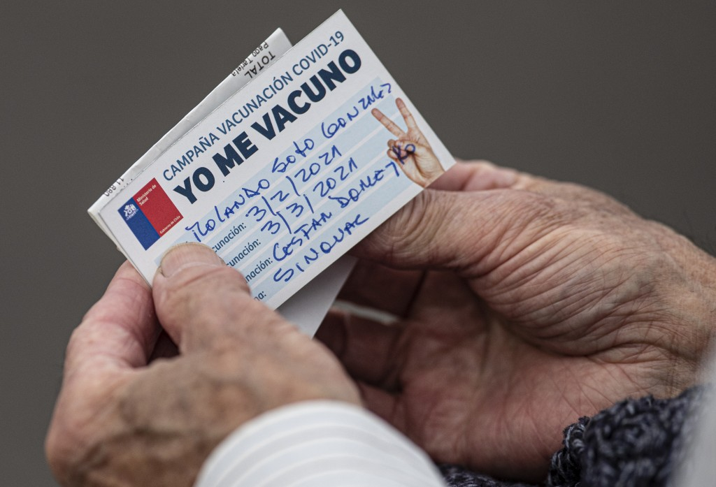 FILE - In this Wednesday, Feb. 3, 2021, file photo, an elderly man looks at his vaccination card after getting a shot of the CoronaVac vaccine for COV...