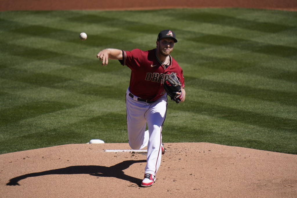 Arizona Diamondbacks starting pitcher Merrill Kelly throws against the Milwaukee Brewers in the first inning of a spring baseball game in Scottsdale, ...