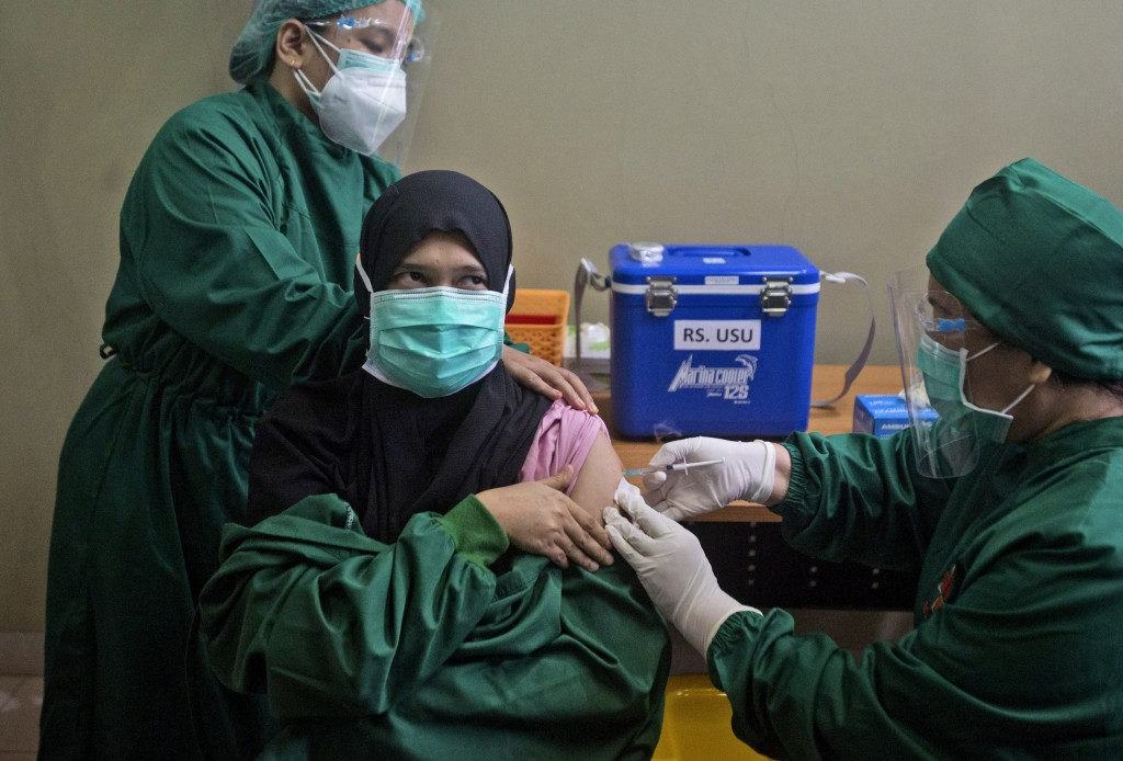 FILE - In this Wednesday, Jan. 20, 2021 file photo, Dr. Lili Rahmawaty, right, gives a shot of COVID-19 vaccine to a colleague at North Sumatra Univer...