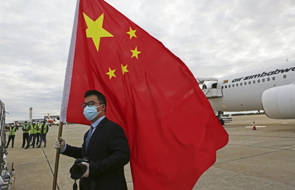 FILE - In this Monday, Feb, 15, 2021 file photo, an official from the Chinese embassy in Zimbabwe holds a Chinese flag next to a plane carrying Sinoph...