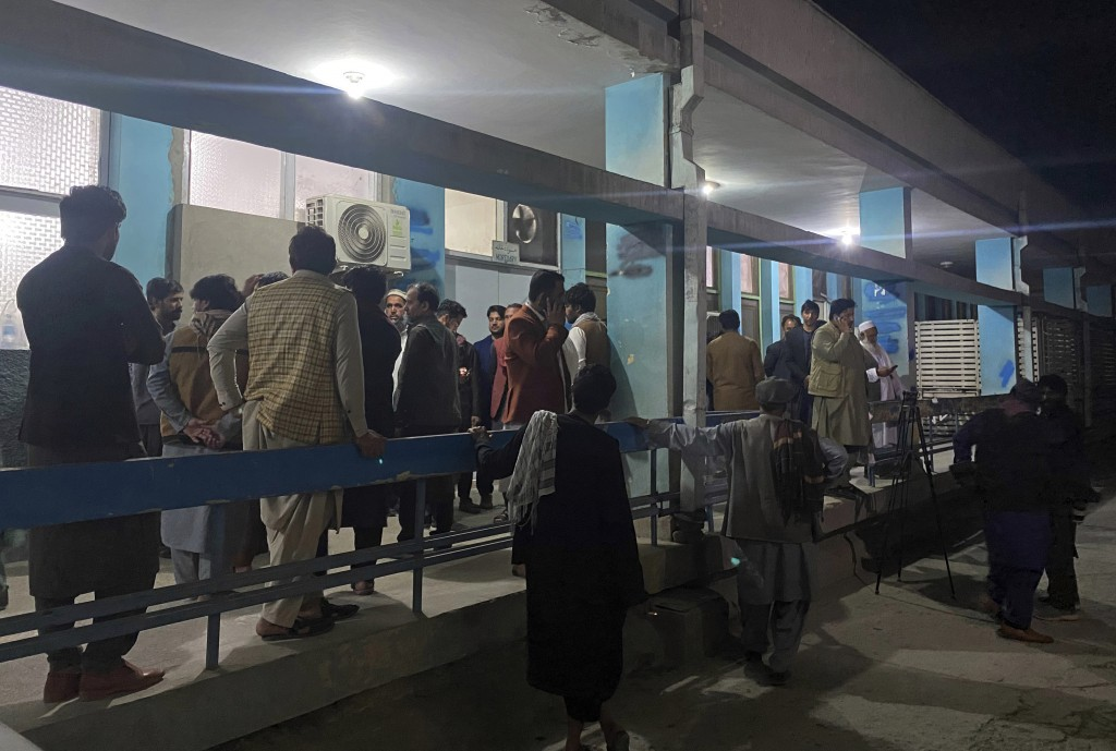 Relatives wait outside a hospital for the bodies of three women that ware killed by gunmen in the city of Jalalabad east of Kabul, Afghanistan, Tuesda...