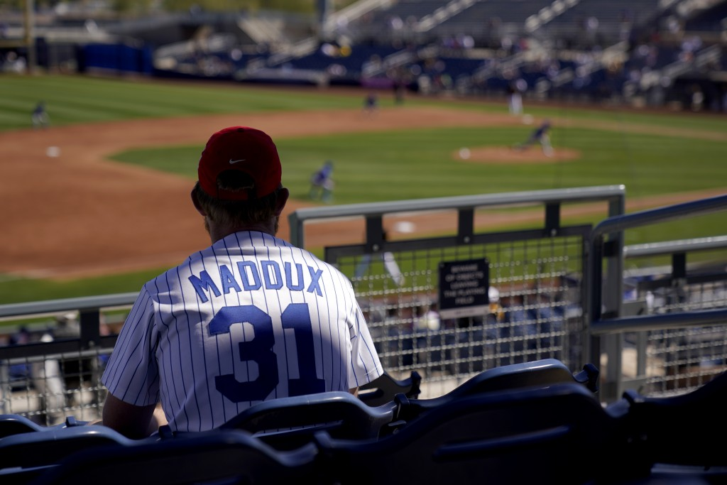A Chicago Cubs fan watches during the third inning of a spring training baseball game against the San Diego Padres, Monday, March 1, 2021, in Peoria, ...