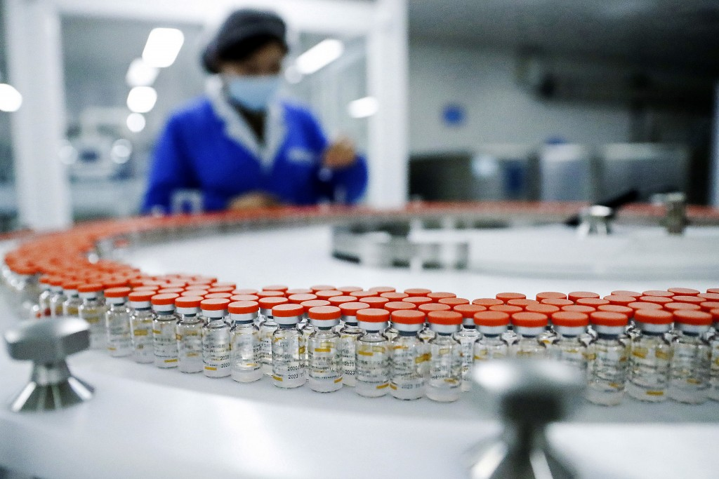 FILE - In this Dec. 23, 2020, file photo released by China's Xinhua News Agency, a Sinovac worker checks the labeling on vials of COVID-19 vaccines on...