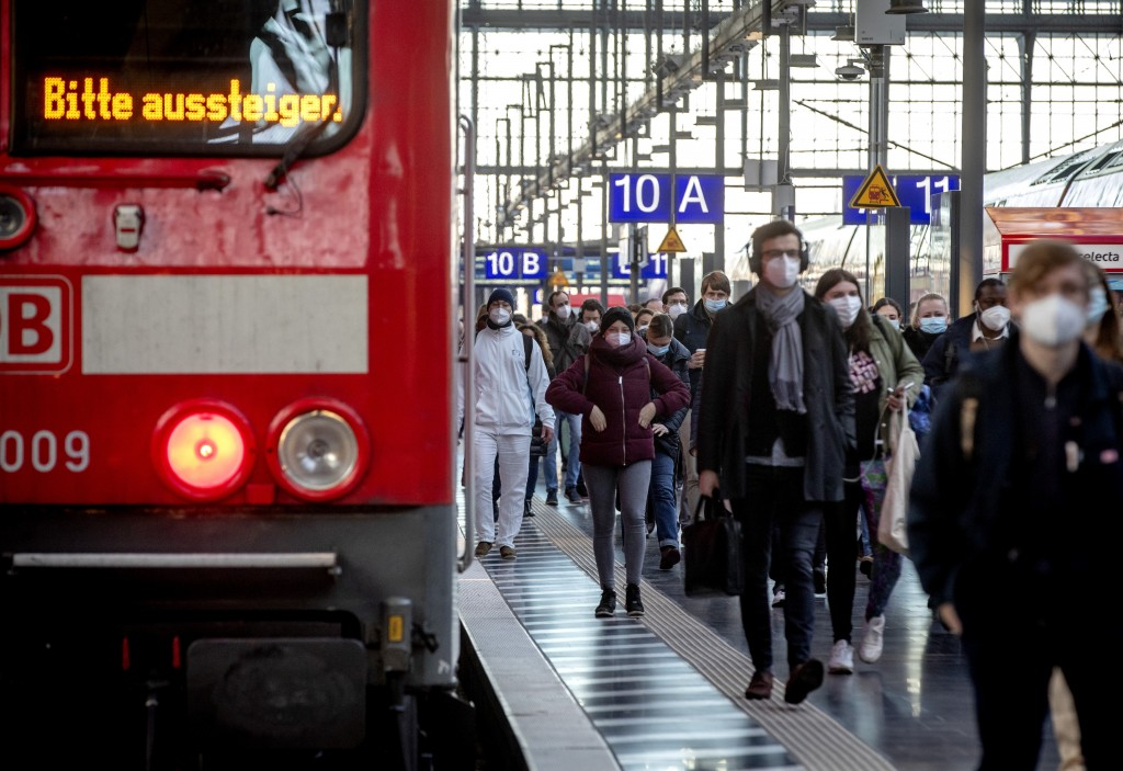 Commuters wearing face masks walk on a platform in the main train station in Frankfurt, Germany, Tuesday, March 2, 2021. German politics discusses fur...