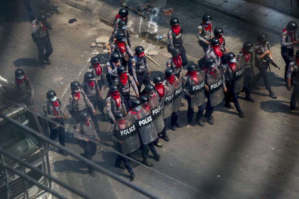 Policemen armed with guns, sling-shots and shields advance towards anti-coup protesters in Mandalay, Myanmar, Wednesday, March 3, 2021. Demonstrators ...