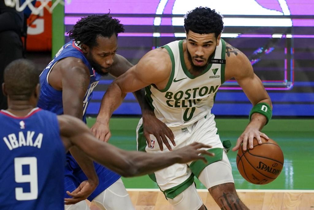 Boston Celtics forward Jayson Tatum (0) drives against Los Angeles Clippers guard Patrick Beverley, left, and center Serge Ibaka (9) in the third quar...