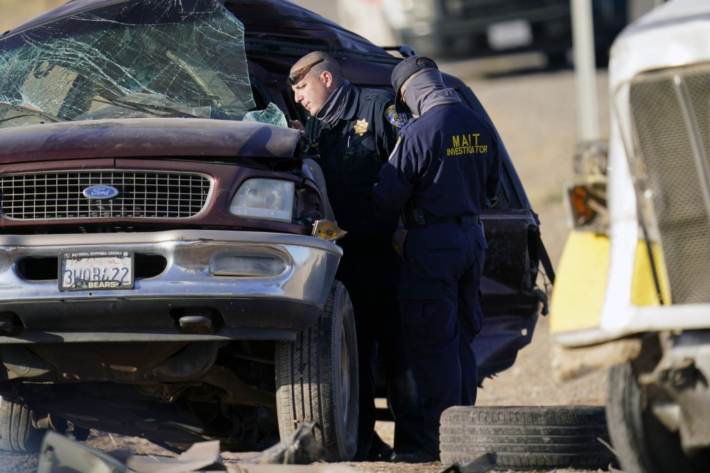 Law enforcement officers sort evidence and debris at the scene of a deadly crash in Holtville, Calif., on Tuesday, March 2, 2021. Authorities say a se...