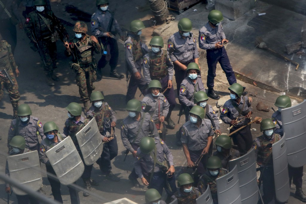 Policemen and soldiers armed with guns and sling-shots advance towards anti-coup protesters in Mandalay, Myanmar, Wednesday, March 3, 2021. Demonstrat...