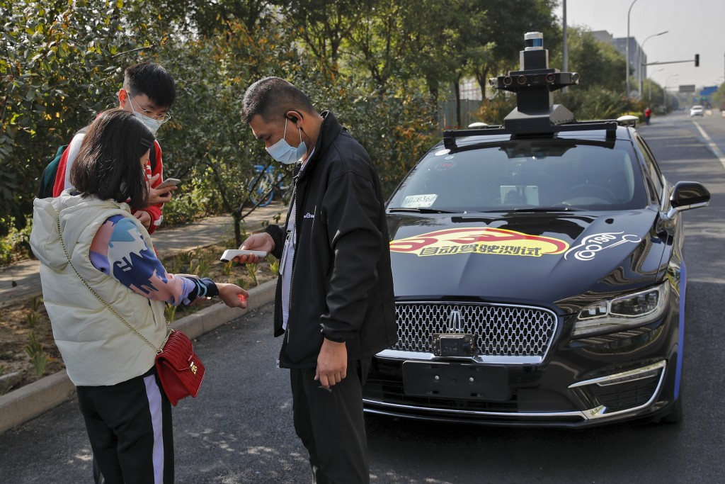 A couple wearing face masks to help curb the spread of the coronavirus gets temperature check before they try out the self-driving ride-hailing servic...