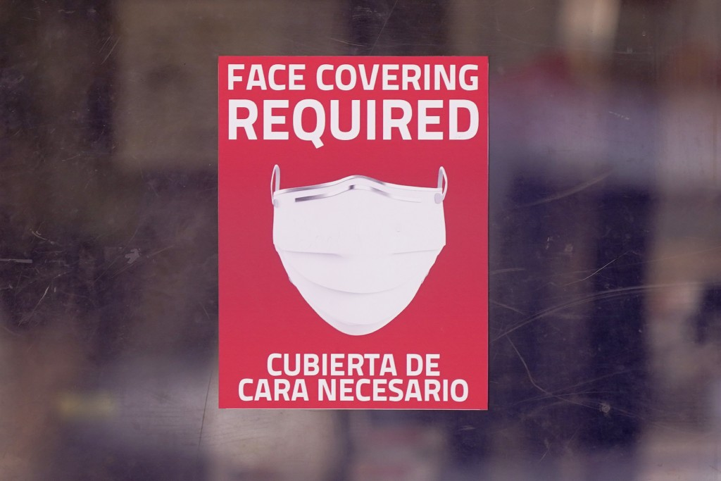 A mask required sign is displayed on the entrance to a business Tuesday, March 2, 2021, in Dallas. (AP Photo/LM Otero)