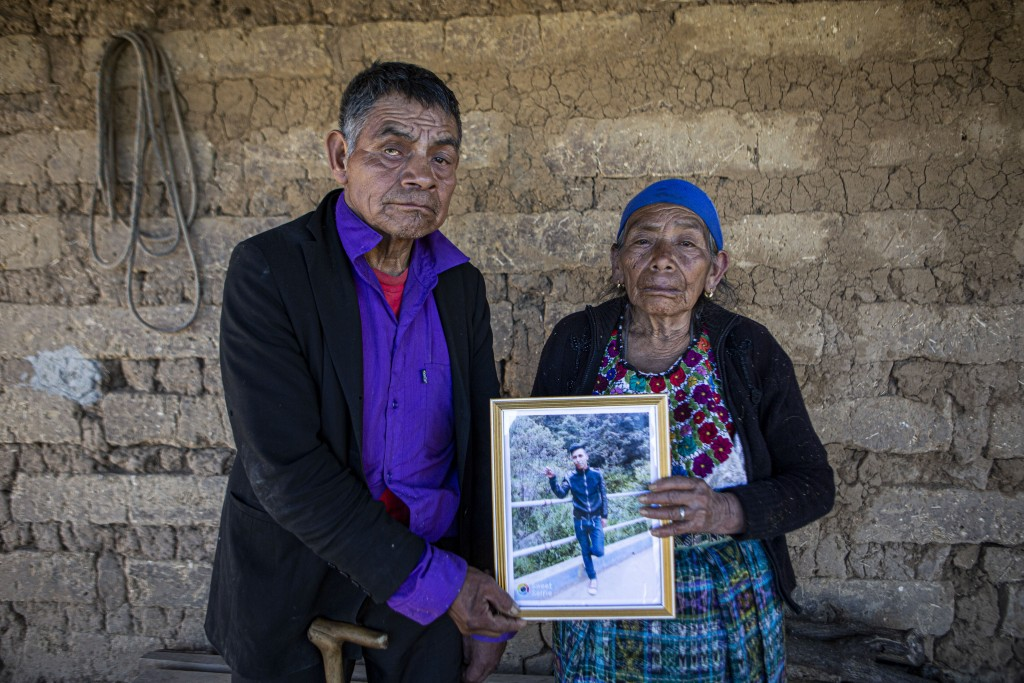 FILE - In this Jan. 27, 2021 file photo, German and Maria Tomas pose for a photo holding a framed portrait of their grandson Ivan Gudiel who they beli...