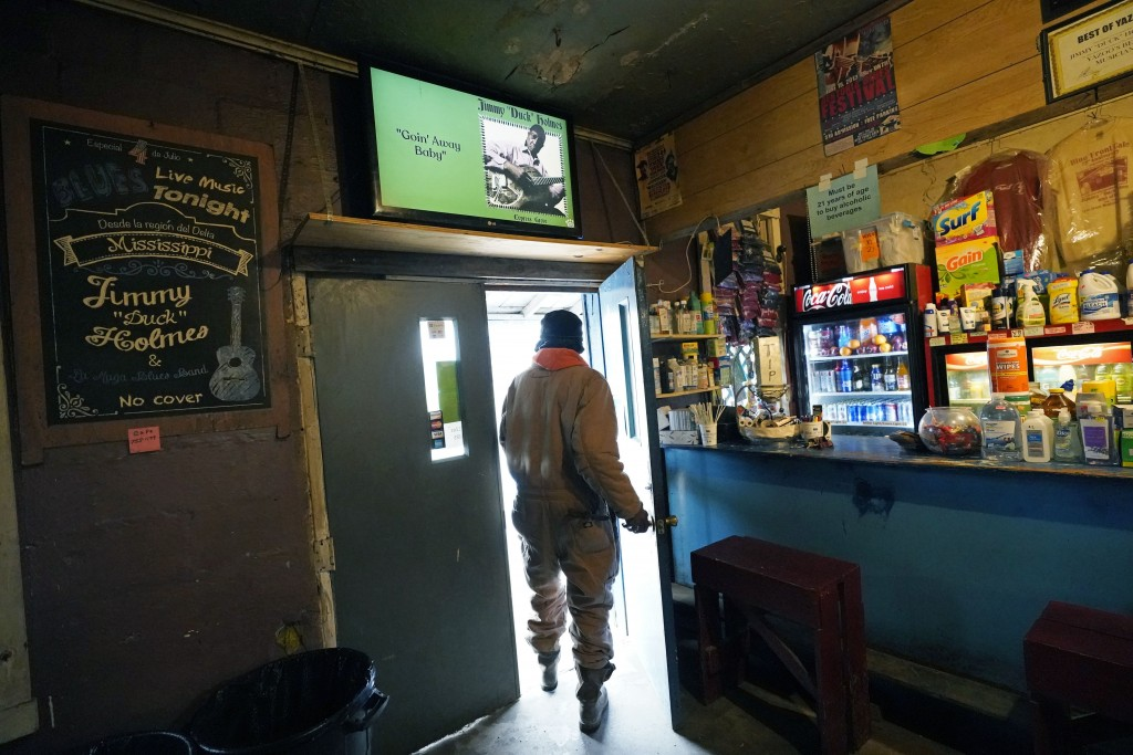 """A customer walks out of the Blue Front Cafe in Bentonia, Miss., while a YouTube video of owner and bluesman Jimmy """"Duck"""" Holmes plays on the televisio..."""