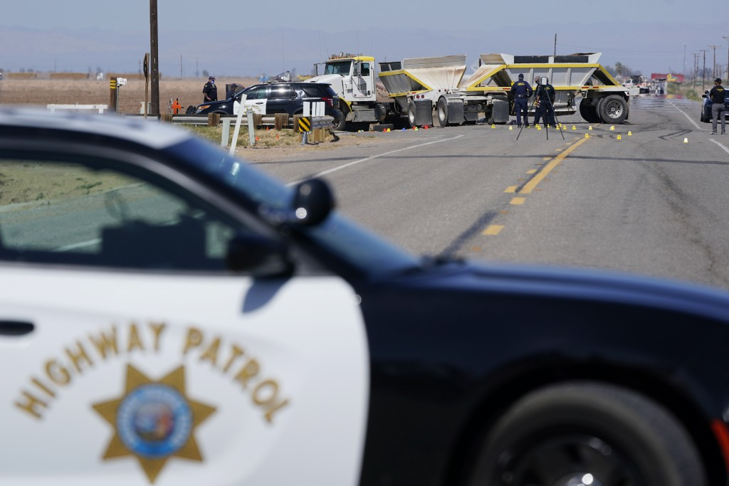 Law enforcement officers work at the scene of a deadly crash in Holtville, Calif., on Tuesday, March 2, 2021. Authorities say a semi-truck crashed int...