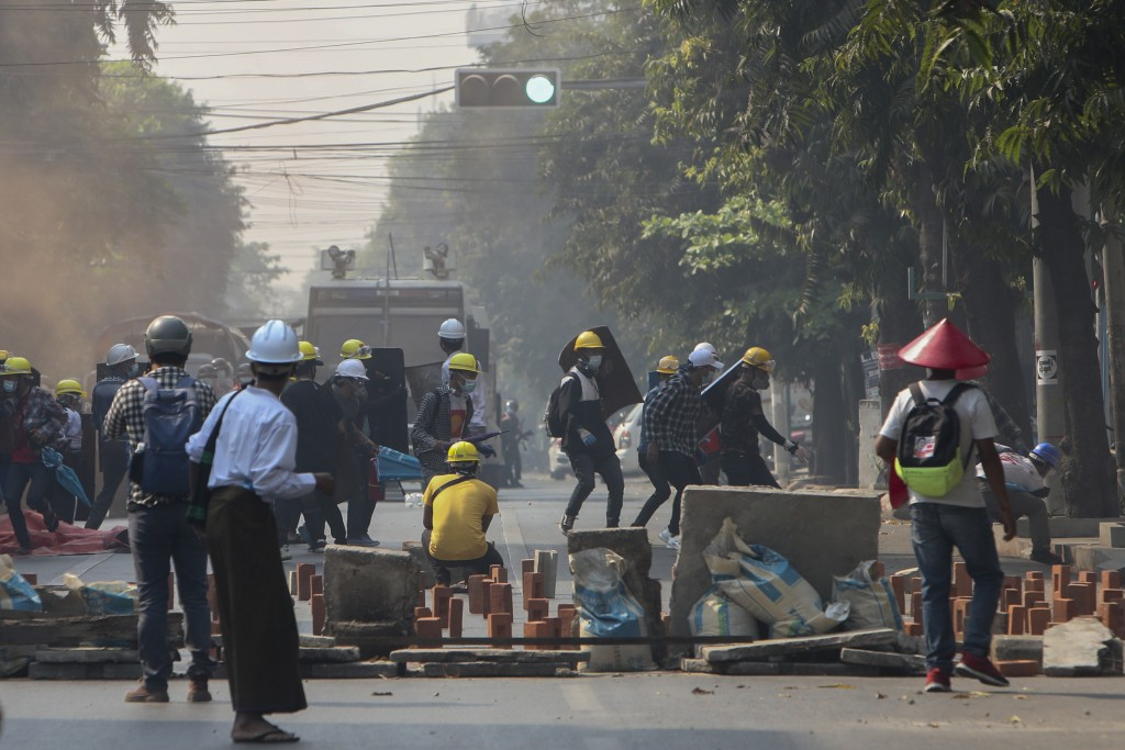 Anti-coup protesters standing behind makeshift-shields brave teargas in Mandalay, Myanmar, Wednesday, March 3, 2021. Demonstrators in Myanmar took to ...