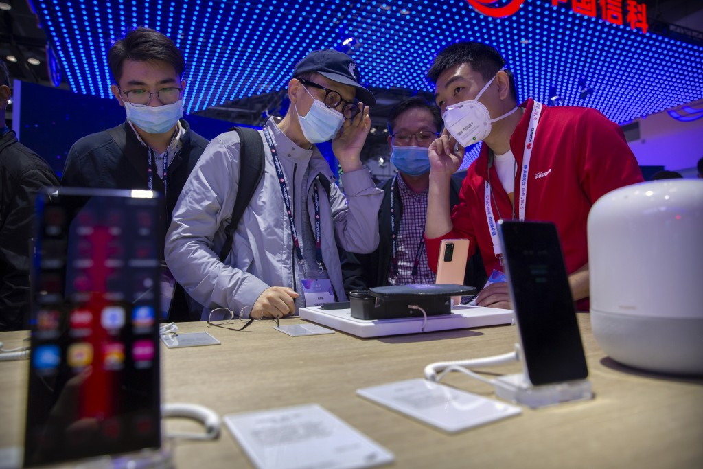 People wearing face masks to protect against the spread of the coronavirus look at smartphones and consumer electronics from Chinese technology firm H...
