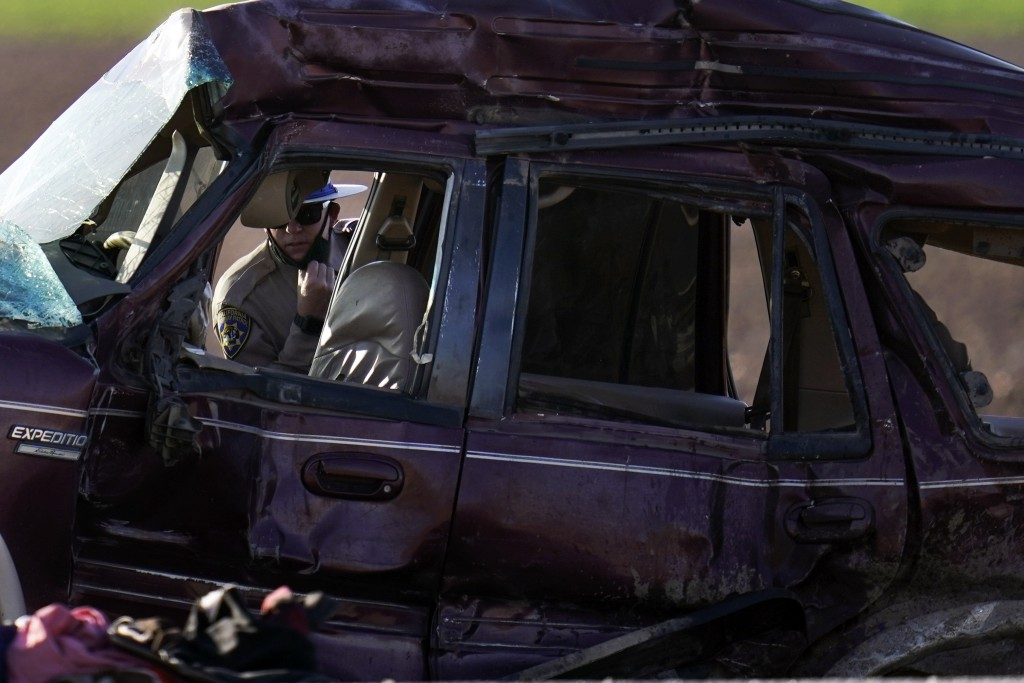 A California Highway Patrol officer examines the scene of a deadly crash in Holtville, Calif., Tuesday, March 2, 2021. Authorities say a semitruck cra...